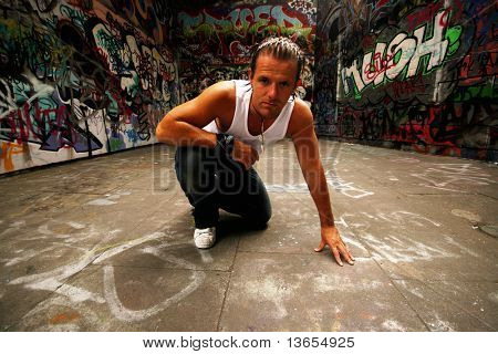 Sexy Model posing in front of urban graffiti sprawl