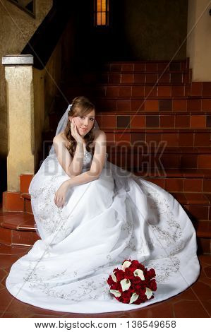A beautiful bride rests her chin in her hand as she waits on a staircase before her wedding.