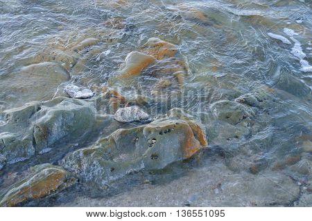 Water over rocks in Pacific Ocean near coast of Ecuador