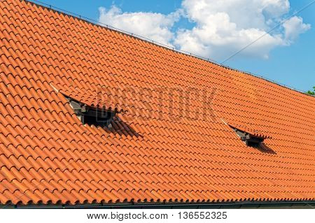 Traditional clay tile roof in sunny day. Roofing works construction background.