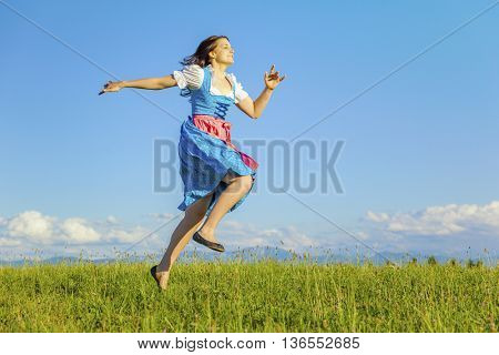 A woman in bavarian traditional dirndl jumping in the nature