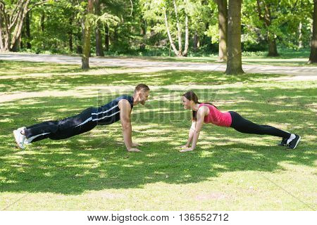 Young Happy Athletic Couple Doing Push-ups In Park