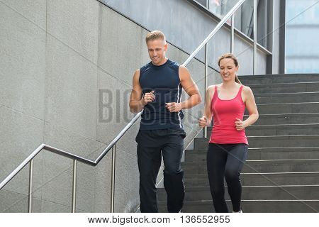 Young Happy Couple Running Together On Stairs