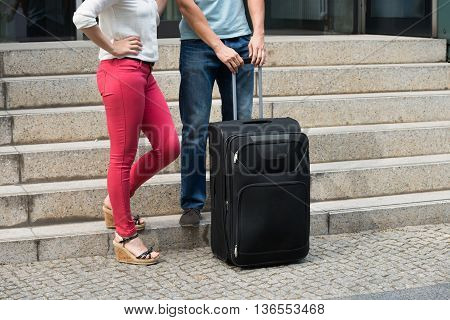 Close-up Of Young Couple Standing With Luggage Near Staircase