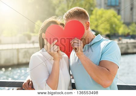 Close-up Of Young Couple Hiding Behind Heart Shape