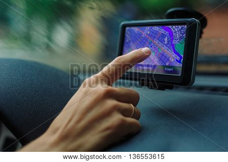 woman looking road on the map GPS Navigator sitting behind the wheel of a car on a rainy day