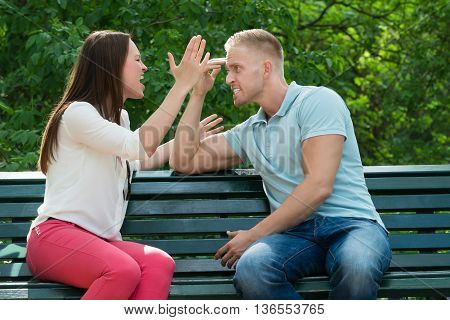 Young Couple Sitting On Bench Quarreling With Each Other At Park
