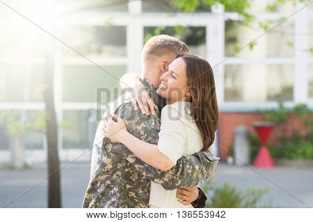Portrait Of Happy Wife Hugging Her Husband In Army Uniform