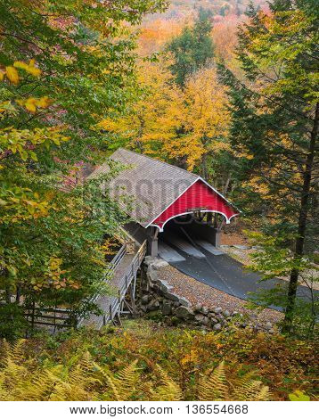 The red covered wooden bridge across the Pemigewasset River in the White Mountains of New Hampshire stands out against colorful autumn foliage.