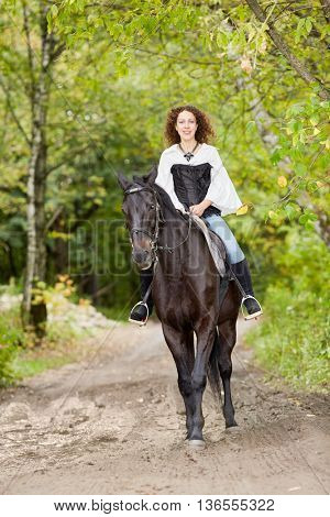 Smiling woman with curly hair rides on bay horse in the park.
