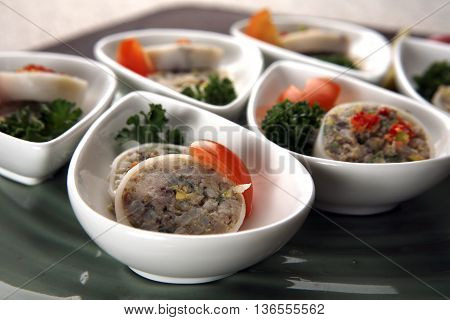 Chinese royal sliced spring rolls with tomato in white cups on the plate