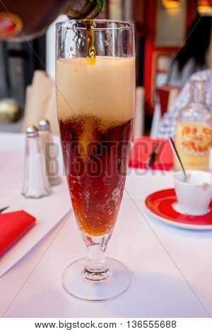 Pouring dark beer into glass at restaurant