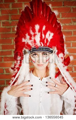 Portrait of young woman dressed in costume made of red and white feathers on head and arms.