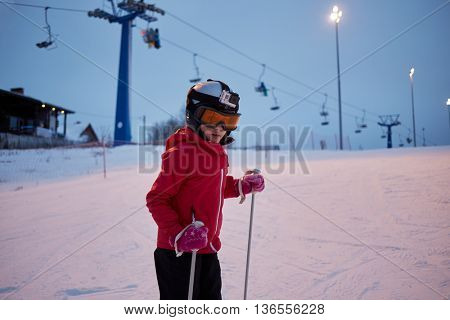 Girl in helmet with camera skiing on snowy slope at ski resort in evening.