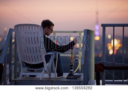 Young man adjusts hookah cap sitting in armchair on highrise roof at sunset dusk.