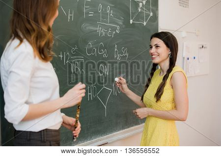 pretty young female college student writing on the chalkboard blackboard during a chemistry class.
