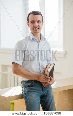 Portrait of young man holding books, looking at camera.