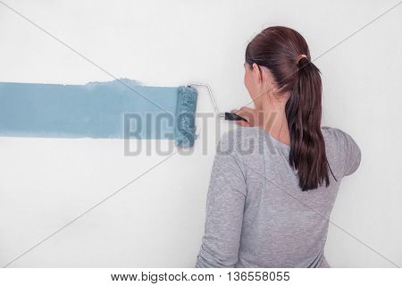 female decorating with color a wall