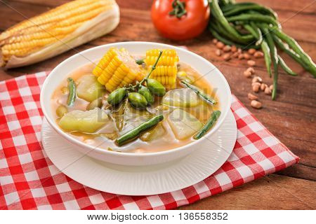 Bowl soup of vegetables with corn and green pumpkin on the table in restaurant