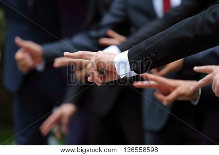group of men in suits show different hand gestures