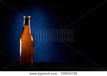 cold beer in bottle isolated on black with blue