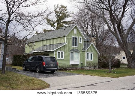 HARBOR SPRINGS, MICHIGAN / UNITED STATES - DECEMBER 24, 2015: A Dodge Grand Caravan is parked beside a green home in Harbor Springs on Christmas Eve.