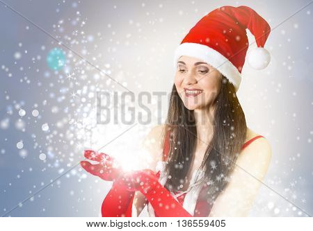 Attractive woman in Santa Clause outfit blowing the Christmas wishes