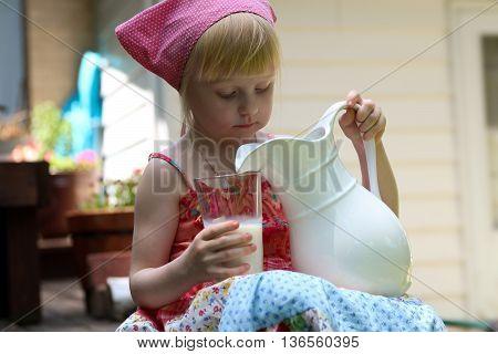 blonde girl drinking milk outside. Houses background behind