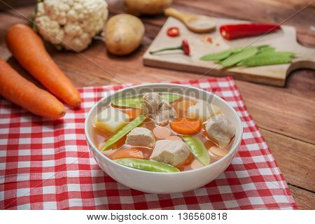 Bowl soup of vegetables with pork green beans and pumpkin on the table in restaurant