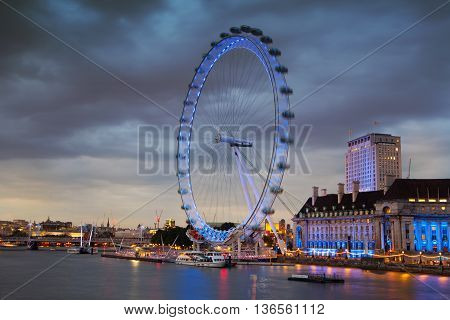 LONDON, UK - JULY 21, 2014: London eye in the night and south bank of river Thames, famous London's walk and tourist destination