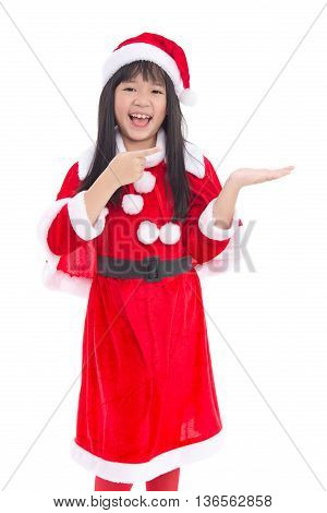 Beautiful asian girl wearing Santa Claus uniform pointing to open hand palm on white background isolated