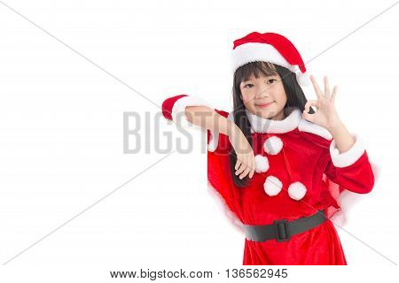 Little asian girl in in Santa Claus uniform showing ok sign with an empty banner isolated on white