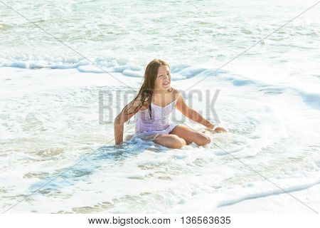 Happy little girl swimming in water beach girl playing in the ocean