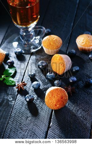 Tea cup, muffins and blueberry on a black wooden table