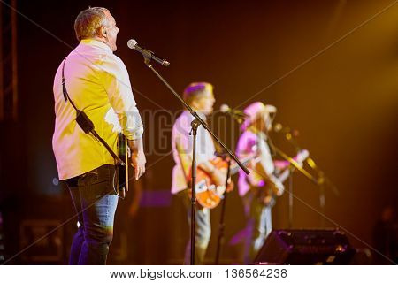 MOSCOW, RUSSIA - APR 24, 2015: Nikolay Fomenko with guitar singing in concert on stage of Crocus city hall at Secret band show. Rock and roll band Secret founded in 1982 in Leningrad.