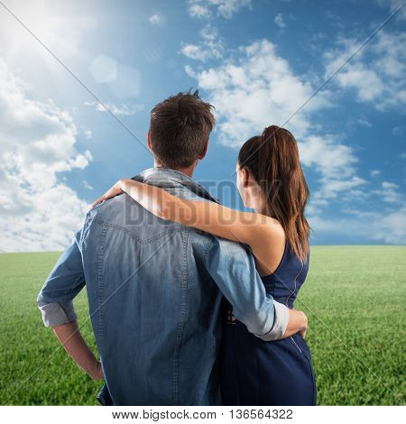 Couple embracing in a field of grass