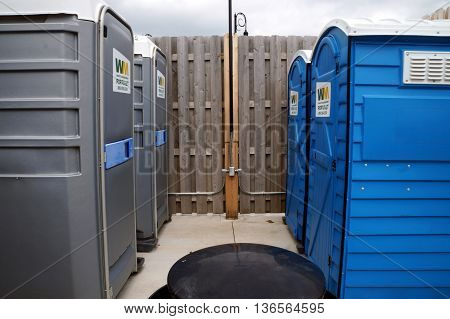 SHOREWOOD, ILLINOIS / UNITED STATES - AUGUST 30, 2015: Members of the public may use portable toilets behind a tall wooden fence, just outside the Village of Shorewood Village Hall.