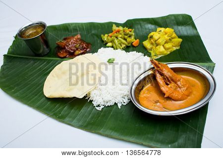 Indian meal with curry shrimp and plain rice on banana leaf tray