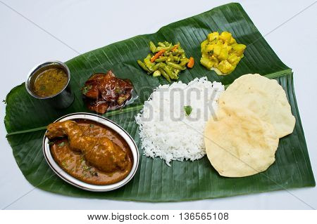 Indian meal with braised chiken and plain rice on banana leaf tray
