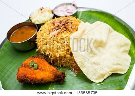 Indian meal with fish and fried rice on banana leaf tray
