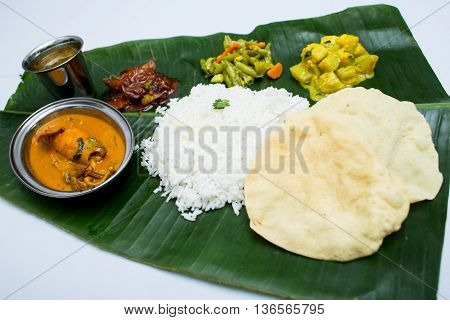 Indian meal with curry squid and plain rice on banana leaf tray