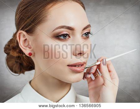 Hand of visagiste applying lipstick on female lips on gray wall background