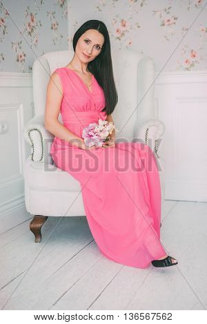 brunette girl in pink dress sitting in a white armchair with a bouquet in their hands