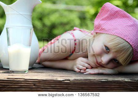 blonde girl drinking milk outside. Green background behind