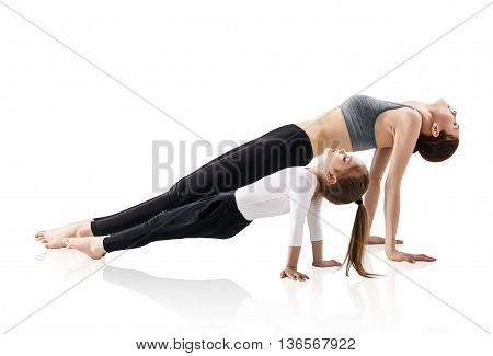 Mother and daughter doing yoga exercise isolated on white