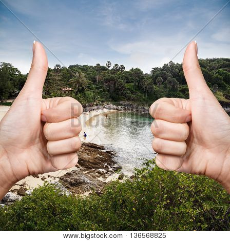 Female hand showing thumb up sign on the beach background
