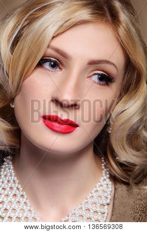 Beautiful blonde girl face with make-up. Closeup portrait