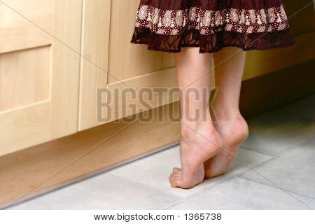 Ein paar Füße auf Tip-Toes, die versuchen, etwas weiter entfernt zu erreichen.