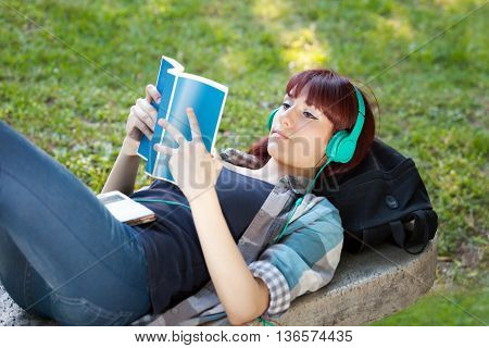 Girl lying on the bench law book and listening to music on headphones.