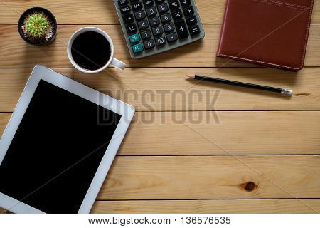 Office stuff with blank screen tablet leather notebook pencil calculator and cup of coffee.Top view with workspace. flat lay image.